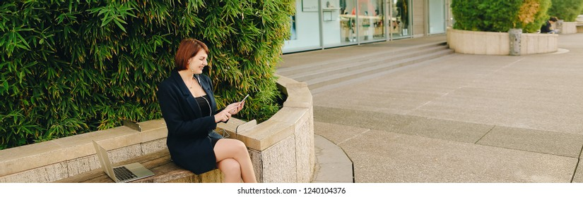 Businesswoman listening to music and chatting with smartphone and in ear phones outside. Concept of resting and having break by biz person. Gladden woman sitting near green plant.