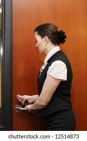 Businesswoman locking a door.