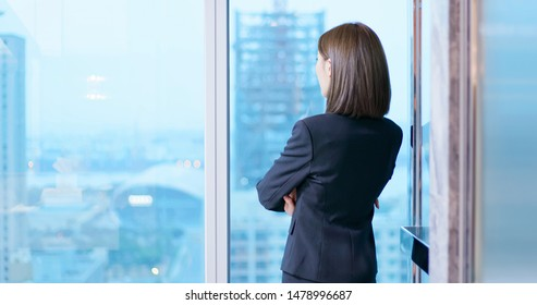 businesswoman look outside through the windor and ponder