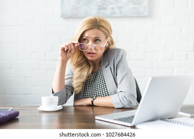 businesswoman looking away above glasses in office