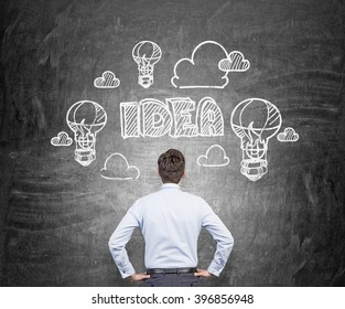 Businesswoman looking at blackboard, idea bulbs and clouds drawn over his head. Back view. Concept of new idea.