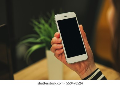 Businesswoman looking at blank screen of white smartphone device in office, display can be used as mock up image for mobile banking, payment, commerce, shopping or business and technology theme.