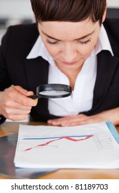 Businesswoman looking at a chart with a magnifying glass in her office