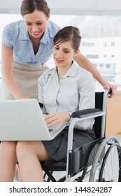 Businesswoman looking at co workers laptop who is sitting in wheelchair in the office