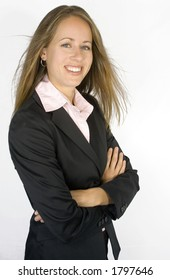 A businesswoman is looking confident while she stands with her arms crossed.