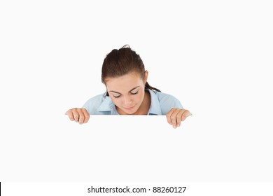 Businesswoman looking down on sign against a white background