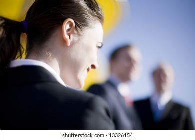 businesswoman looking forward with two businessmen looking at camera
