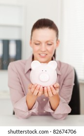 A businesswoman is looking at her piggy bank in her office