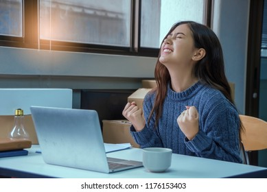 Businesswoman looking at laptop excited by good job and good news online, lucky successful winner  sitting at office desk raising hand in Yes  celebrating business success win result.