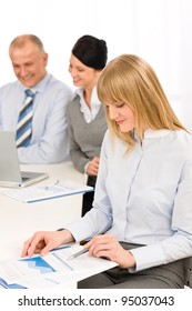 Businesswoman looking at report at team meeting with colleagues