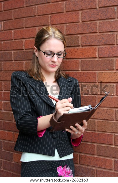 Businesswoman looking at schedule in front of office building
