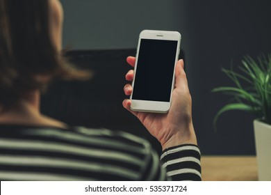 Businesswoman looking at smartphone blank screen as copy space in business office interior