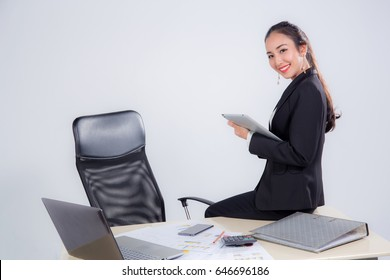 businesswoman looking tablet with sitting table in office on white background.