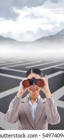 Businesswoman looking through binoculars against cloudy sky over maze