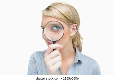 Businesswoman looking through magnifying glass and smiling