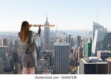 Businesswoman looking through a telescope against city skyline