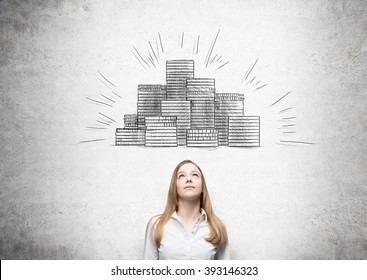 Businesswoman looking up, picture of coin piles drawn over her head. Concrete background. Concept of making money.
