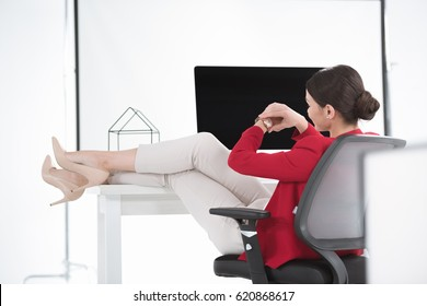 businesswoman looking at watch while sitting at workplace