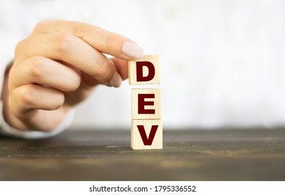 Businesswoman made word DEV with wood building blocks.