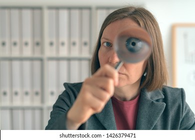 Businesswoman with magnifying glass doing business financial auditing, examination and evaluation of financial statements.