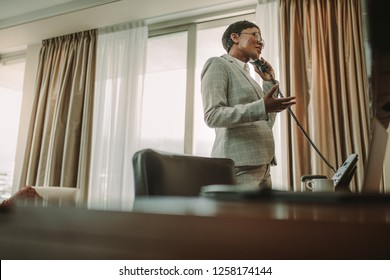 Businesswoman making call from hotel room. Businesswoman in formals talking over landline phone, working from hotel room while on business trip.