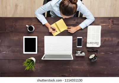 Businesswoman making to do list on notebook