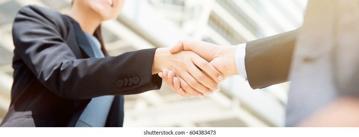 Businesswoman making handshake with a businessman, female leader concept - panoramic web banner