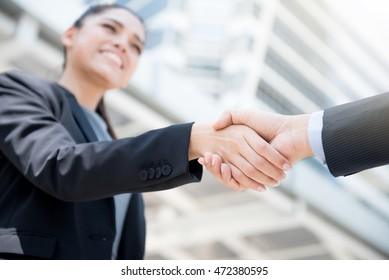 Businesswoman making handshake with a businessman -greeting, dealing, merger and acquisition concepts