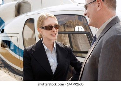 Businesswoman and man in discussion by helicopter