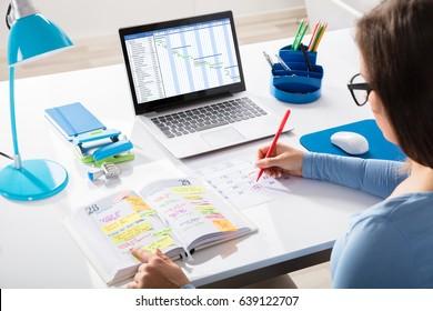 Businesswoman Marking Schedule On Calendar With Gantt Chart On Laptop Screen