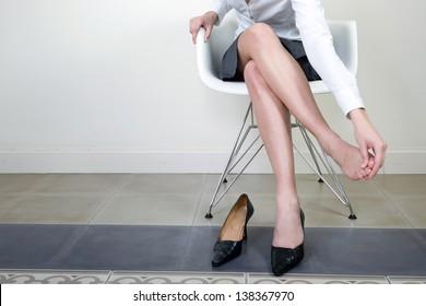 Businesswoman massaging her foot