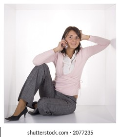 businesswoman with mobile phone in the cramped white cube