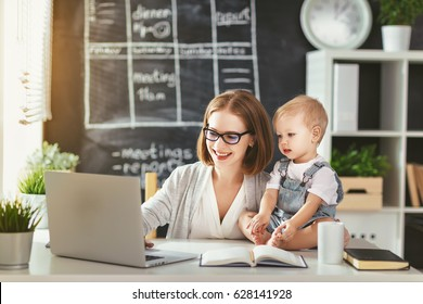 Businesswoman mother  woman with a toddler working at the computer