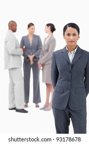 Businesswoman with negotiating trading partners behind her against a white background
