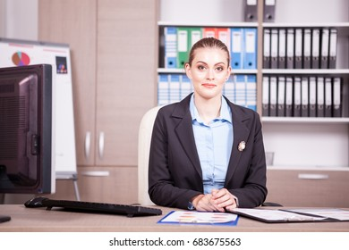 Businesswoman in an office with charts on table. Business and finance