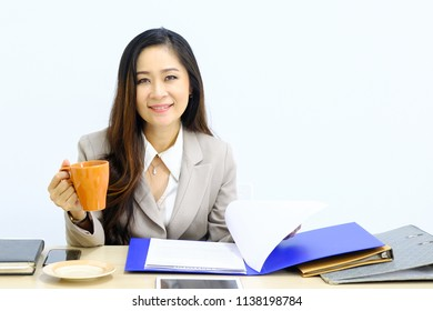 Businesswoman in office with coffee in orange cup