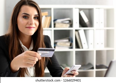 Businesswoman in the office holds a plastic credit debit card in her hand portrait. Makes online purchases content commerce on the Internet shop ecommerce concept
