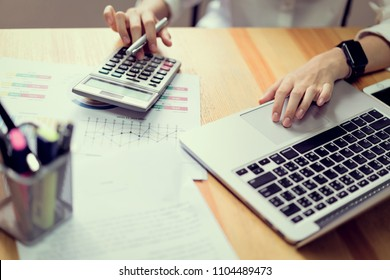 Businesswoman in office and use computer and calculator to perform financial accounting. To plan advance budget.