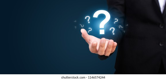 businesswoman on blurred background holding hand question marks