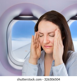 businesswoman on a flight with a great headache
