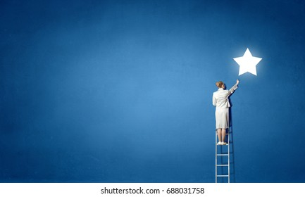 Businesswoman on ladder reaching star
