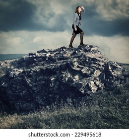 Businesswoman on a mountain top looking into the distance.