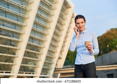 Businesswoman on the phone. Female holding coffee cup outdoor. Coffee break at work.