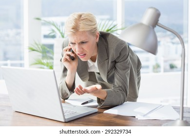 Businesswoman on the phone and using her laptop in an office
