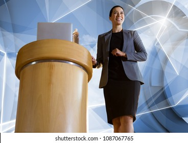 Businesswoman on podium speaking at conference with futuristic shapes