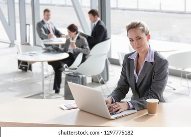 Businesswoman on trip working on laptop in airport lounge looking at camera