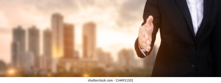 businesswoman open hand ready to seal a deal, partner shaking hands, shaking hands, copy space, city background