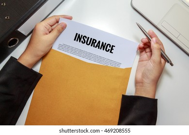 Businesswoman opening Insurance policy document in letter envelope - business concept.