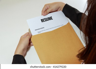 Businesswoman opening resume in letter envelope.