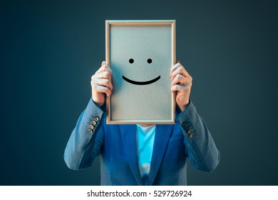 Businesswoman is optimistic about her future in corporate business, holding printed happy smiley emoticon over her face